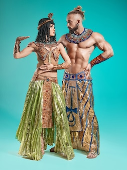 Der mann und die frau in den bildern des ägyptischen pharaos und der kleopatra auf blauem studiohintergrund
