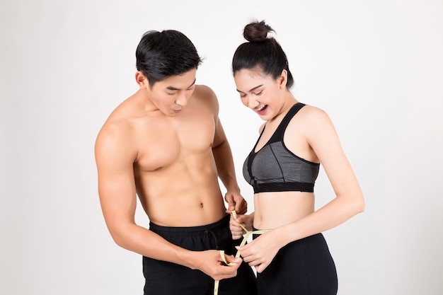 Der mann und die frau messen ihren körper. fitness- und gesundheitskonzept