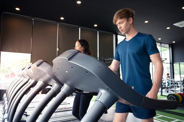 Der mann und frau, die auf maschine laufen, arbeiten für gesundes an der turnhalle aus