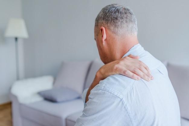 Der mann verzieht den schmerz in seiner schulter