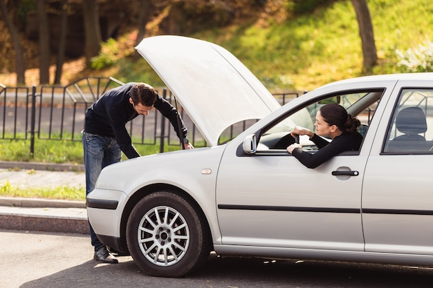 Der mann wollte einer jungen frau helfen, ihr auto zu reparieren, weiß aber nicht, wo das problem liegt