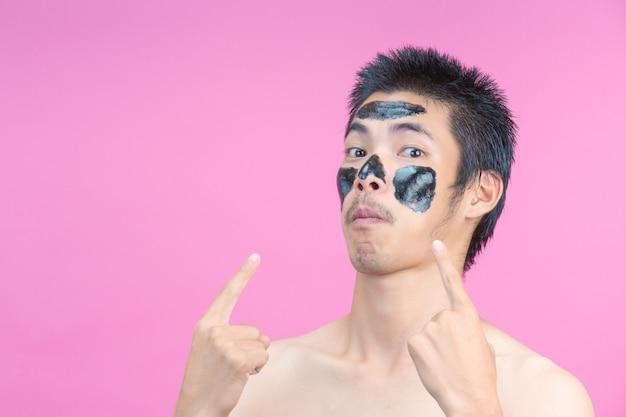 Der mann zeigte mit schwarzer kosmetik und rosa auf sein gesicht.