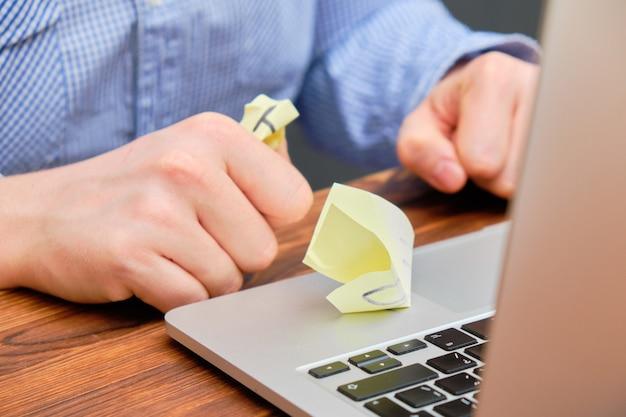 Der mann zerknitterte die aufkleber neben dem laptop. das konzept fehlgeschlagener ideen.