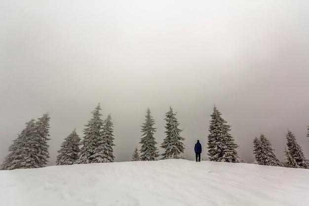 Der mannwanderer, der im winterschnee steht, bedeckte die berge, die ansicht genießen