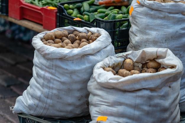 Der markt verkauft eine vielzahl von gemüse und taschen mit kartoffeln.