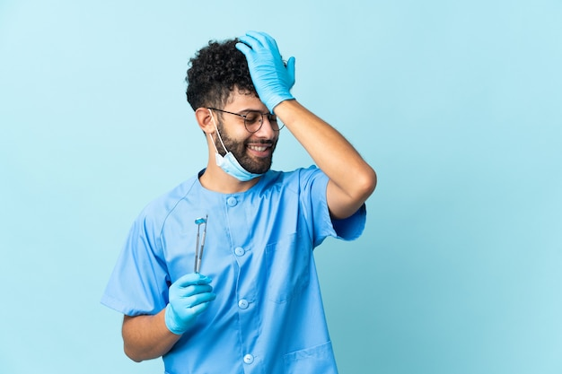 Der marokkanische zahnarzt, der auf blau isolierte werkzeuge hält, hat etwas erkannt und beabsichtigt, die lösung zu finden