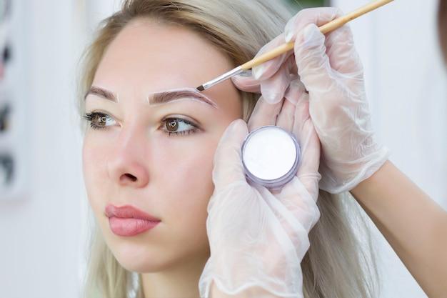 Der maskenbildner macht sich mit einem weißen stift notizen für augenbrauen und malt augenbrauen. professionelles make-up und gesichtspflege. augenbrauen färben.