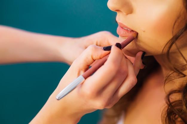 Der maskenbildner trägt make-up auf die lippen der braut auf