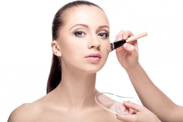 Der maskenbildner trug mit einem foundation-pinsel das gesicht auf. perfekte haut frauen. make-up für brünette