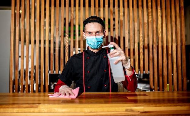 Der maskierte koch desinfiziert den arbeitstisch mit einem antiseptikum