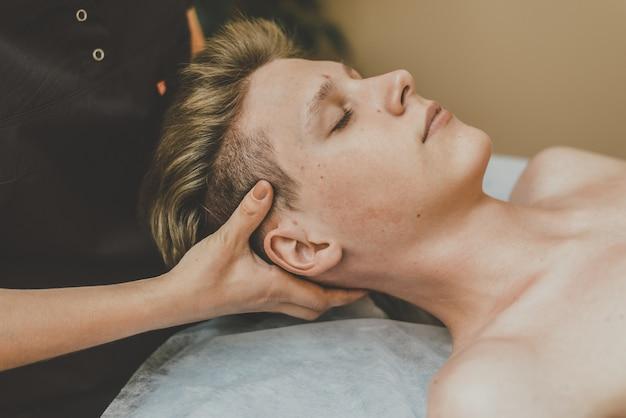 Der masseur macht einem jungen mann eine gesichtsmassage. ein mann wird gesicht auf einem massagetisch massiert