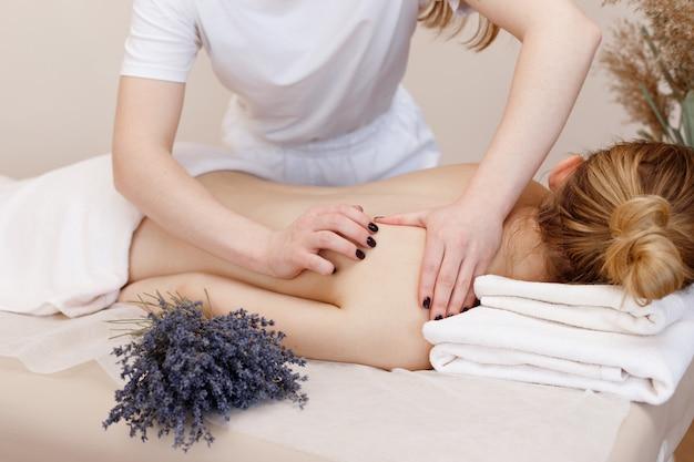 Der masseur massiert den rücken der frau zur entspannung. aromatherapie