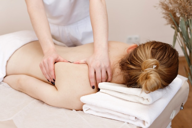 Der masseur massiert den rücken des mädchens. spa-salon