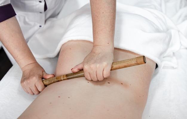 Der masseur verwendet während der behandlung massage-bambusstäbchen.