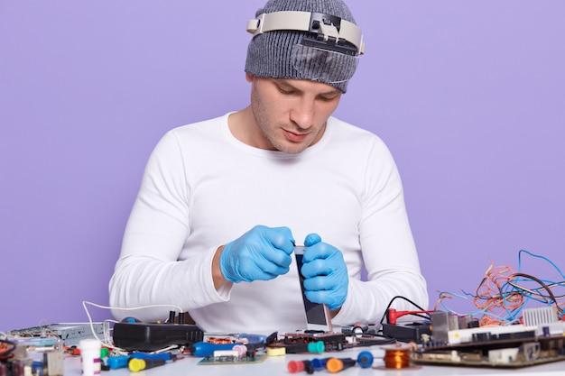 Der master baut das telefon zusammen und repariert es durch ersetzen des neuen akkus und bildschirms