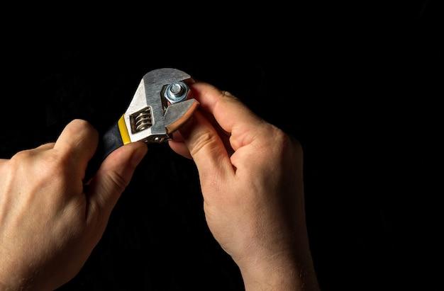 Der master zieht die mutter mit einem verstellbaren schraubenschlüssel in der schraube fest an