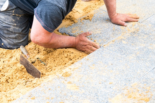 Der maurer legt kiesplatten auf sand, um eine gasse zu bilden