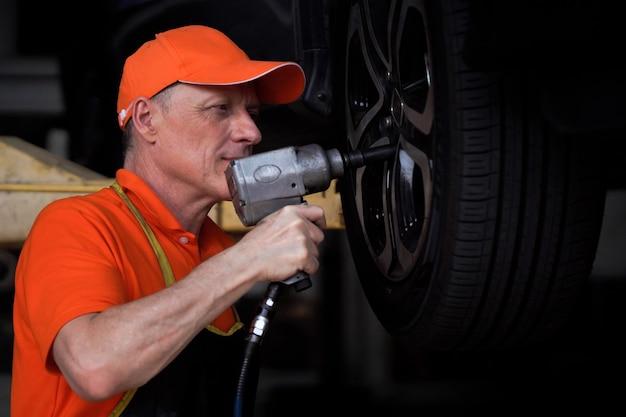 Der mechaniker, der mechaniker, wechselte die reifen und pumpte die reifen auf.