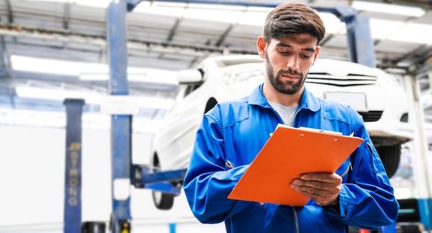 Der mechaniker in blauer arbeitskleidung überprüft die checkliste für die fahrzeugwartung mit einem verschwommenen auto im hintergrund. kfz-reparaturservice, berufliche tätigkeit.