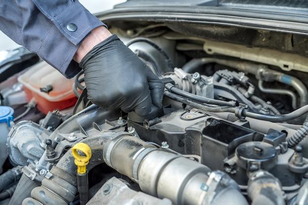 Der mechaniker öffnet den öldeckel für den ölwechsel eines automotors. autoservice