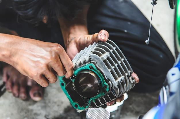 Der mechaniker repariert das motorrad.