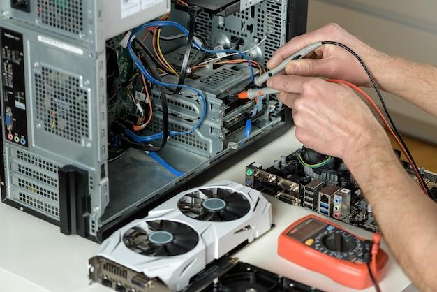 Der mechaniker überprüft die funktionsfähigkeit des computers mit einem multimeter aus der nähe