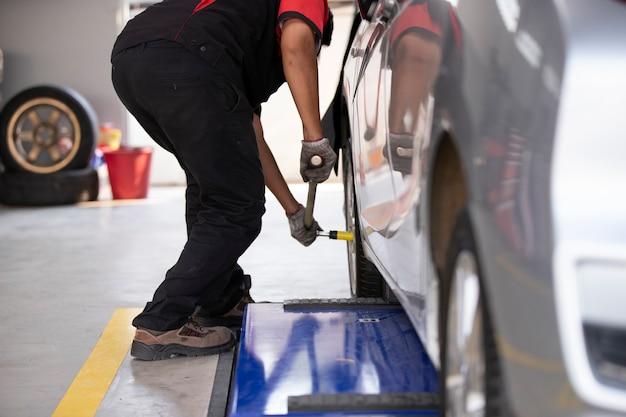 Der mechaniker wechselt die autoreifen für diejenigen, die die reifenmitte benutzen.