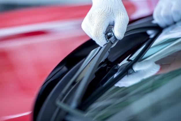Der mechaniker wechselt die scheibenwischer auf dem parkplatz. wechseln sie die scheibenwischerreifen, um sich auf die reinigung der windschutzscheibe vorzubereiten, während es in der regenzeit regnet.