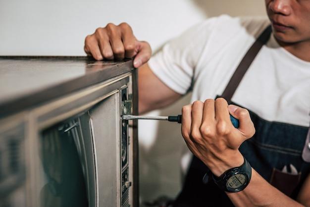 Der mechaniker zieht die schrauben am fernsehgerät mit einem schraubendreher fest.