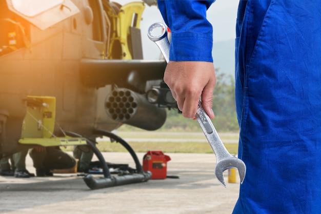 Der mechanikermann, der den schlüssel mit dem parth des kampfflugzeugs hält, ist hintergrund.