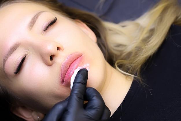 Der meister des permanent make-ups wischt das überschüssige pigment für tattoos von den lippen der models