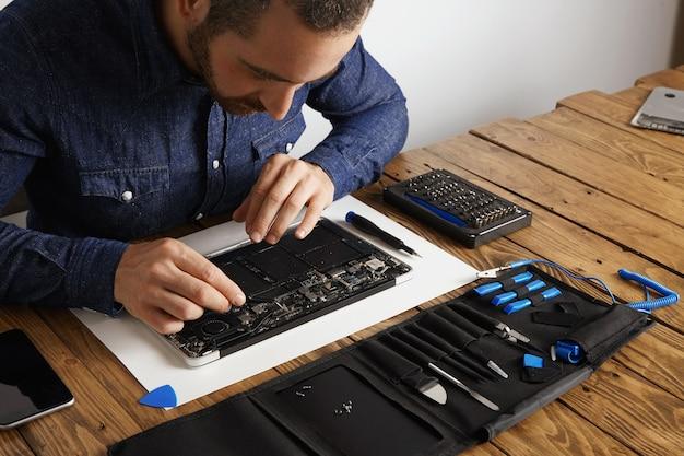 Der meister entfernt mit einer abgewinkelten esd-pinzette staub von den elektronischen platinen eines kaputten, schlanken computer-laptops, um ihn zu reparieren und wieder zum laufen zu bringen