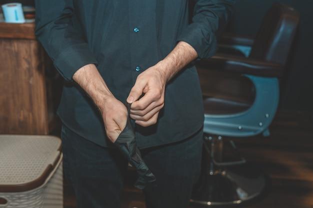Der meister im barbeshop zieht schwarze handschuhe an. friseur für männer.