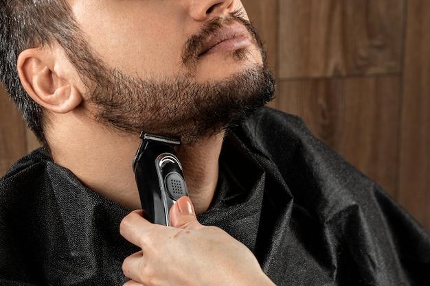 Der meister macht dem kunden einen barthaarschnitt mit einer elektrischen maschine, einem trimmer und einer nahaufnahme. der prozess des rasierens eines bartes beim friseur. körperpflege, lebensstil, metrosexuell.