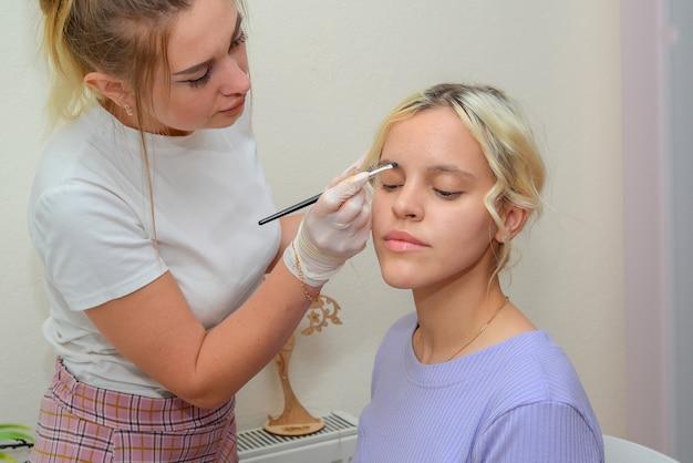 Der meister macht dem kunden make-up in den händen und gesichtern des salons
