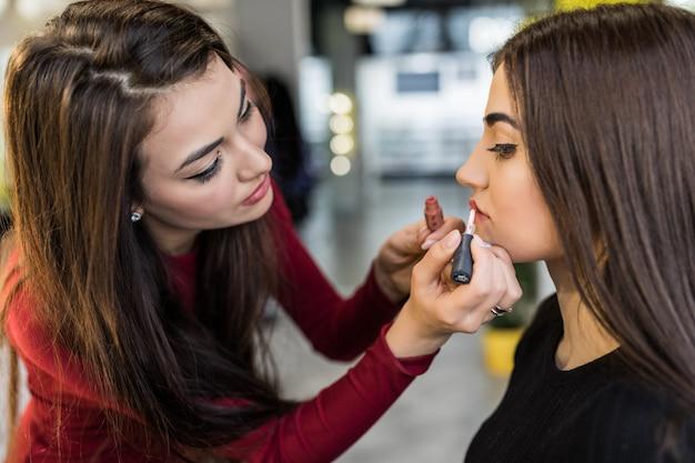 Der meister macht die letzten schritte in der make-up-arbeit mit den großen lippen des models
