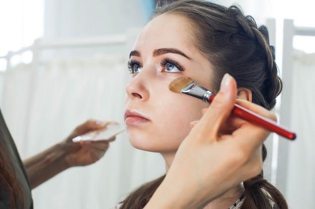 Der meister macht ein schönes blondes make-up in einem schönheitssalon