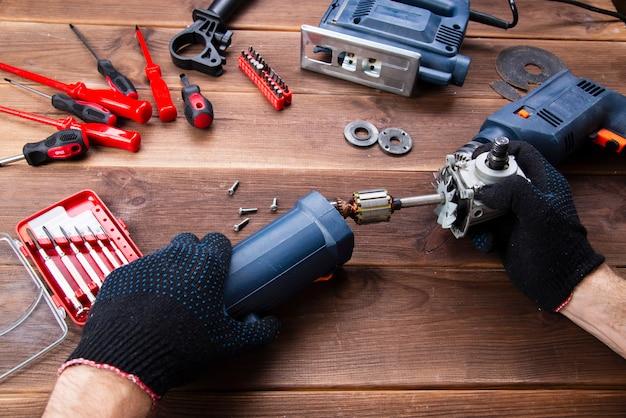 Der meister repariert ein defektes elektrisches gerät: bohrer, fräser auf einem holztisch.