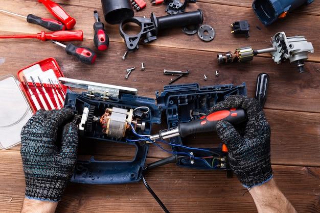 Der meister repariert ein kaputtes elektrogerät: bohrmaschine, cutter auf einem holztisch. reparaturwerkstatt für elektrowerkzeuge