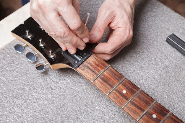 Der meister richtet den gitarrenhalsanker ein