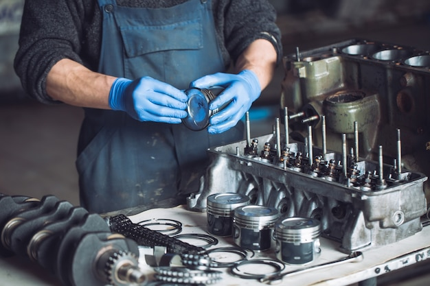 Der meister sammelt einen umgebauten motor für das auto.