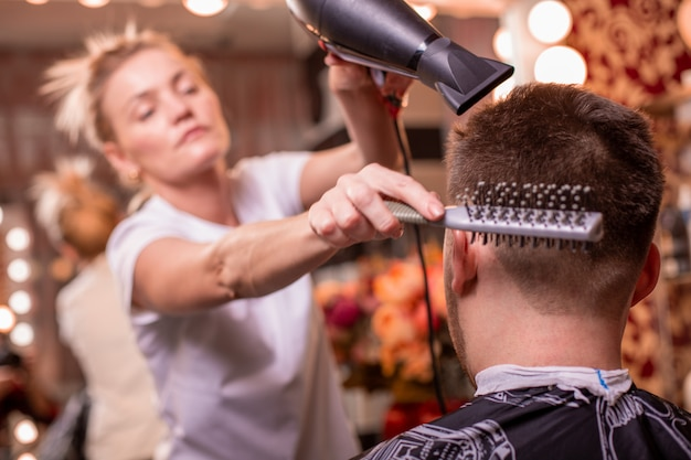 Der meister schneidet die haare und den bart eines mannes in einem friseursalon, ein friseur schneidet die haare für einen jungen mann.