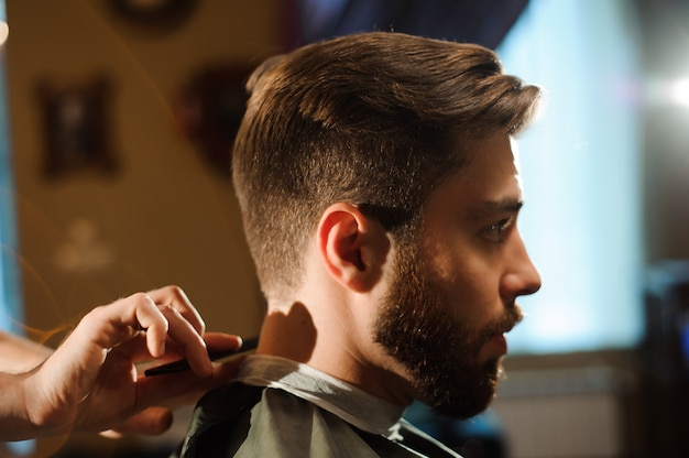 Der meister schneidet im friseursalon haare und bart von männern