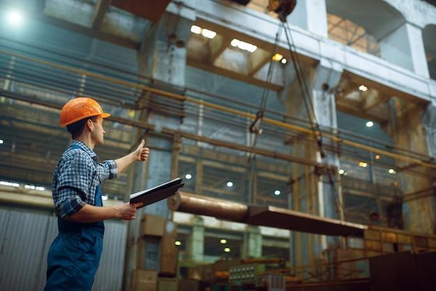 Der meister zeigt dem kranführer in der metallfabrik die daumen nach oben. metallverarbeitende industrie, industrielle fertigung