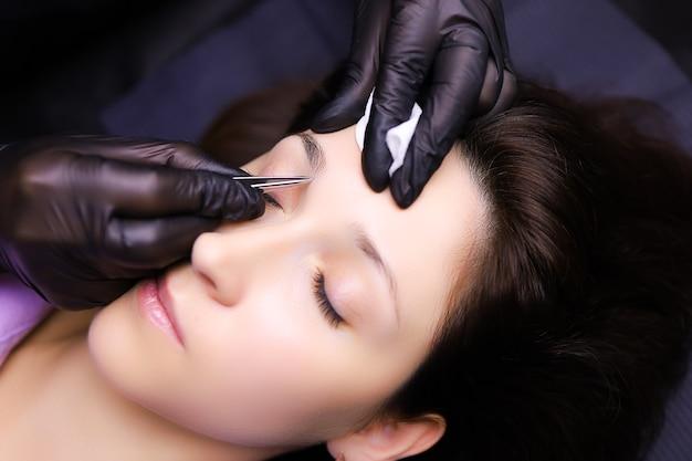 Der meistertätowierer bereitet die augenbrauen zum auszupfen überschüssiger haare vor bereitet die kontur der augenbrauen zum tätowieren vor