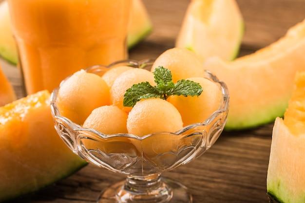 Der melonensaft mit minze in einem glas auf dem tisch. hamamelone