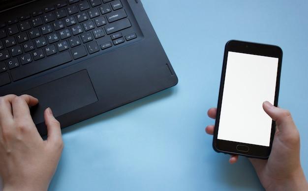 Der mensch arbeitet an einem laptop und hält ein telefon flach in der hand. das problem der konzentration bei der arbeit während der arbeit von zu hause aus. der mann wird durch das telefon abgelenkt, während er von zu hause aus am laptop arbeitet.
