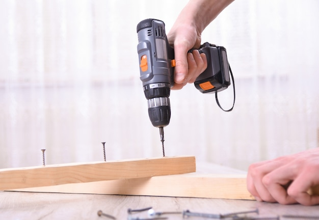 Der mensch arbeitet mit der möbelmontage unter verwendung eines elektrischen schraubendrehers in einer neuen hausinstallation - techniker vor ort arbeitet unter verwendung eines handwerkzeugkonzepts