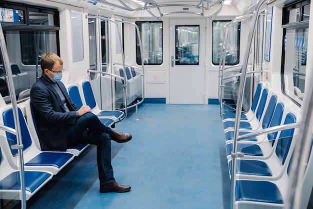 Der mensch benutzt eine medizinische gesichtsmaske, sitzt alleine in der u-bahn, pendelt mit öffentlichen verkehrsmitteln zur arbeit und vermeidet covid-19