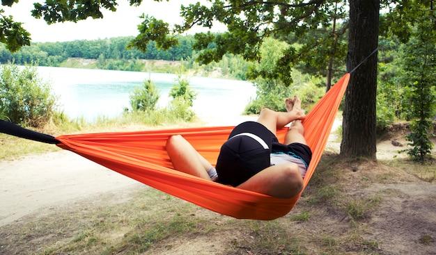 Der mensch entspannt und entspannt sich in der hängematte im lager